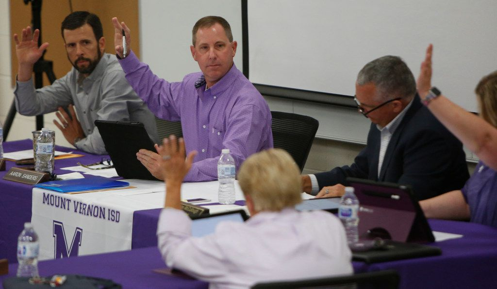 Mount Vernon school board president Aaron Sanders, center, calls for a vote of the board as board member Josh Jordan , far left, casts his vote. The meeting of the Mount Vernon ISD Board was the first since naming Art Briles as its head football coach. The Meeting was held in the High School Lecture Hall in Mount Vernon on June, 17, 2019.  (Steve Hamm/ Special Contributor)