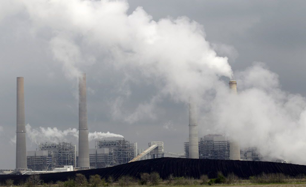 FILE - In this March 16, 2011, file photo, exhaust rises from smokestacks in front of piles of coal in Thompsons, Texas. A federal appeals court on Tuesday ordered the Environmental Protection Agency to relax some limits it set on smokestack emissions that cross state lines and taint downwind areas with air pollution from power plants they can't control.  (AP Photo/David J. Phillip, File) 08042015xPUB