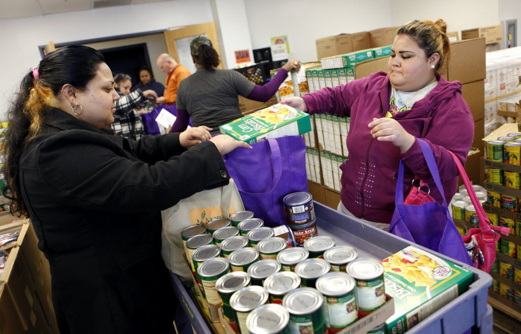 Sisters Florinda Ramirez (left) and Maximina Ramirez pack up their  food donation for their family of ten at Crossroads Community Services in Dallas on Wednesday, January 16, 2013. (Lara Solt/The Dallas Morning News)