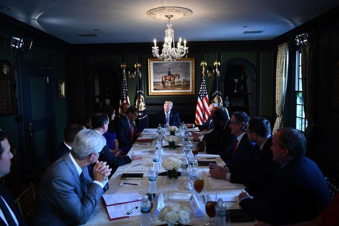 President Donald Trump participates in a roundtable discussion on prison reform, August 9, 2018 in Bedminster, New Jersey. Texas Attorney General Ken Paxton is at right in foreground. Energy Secretary Rick Perry is on the president's right in red tie. (Photo by Brendan Smialowski/AFP/Getty Images)