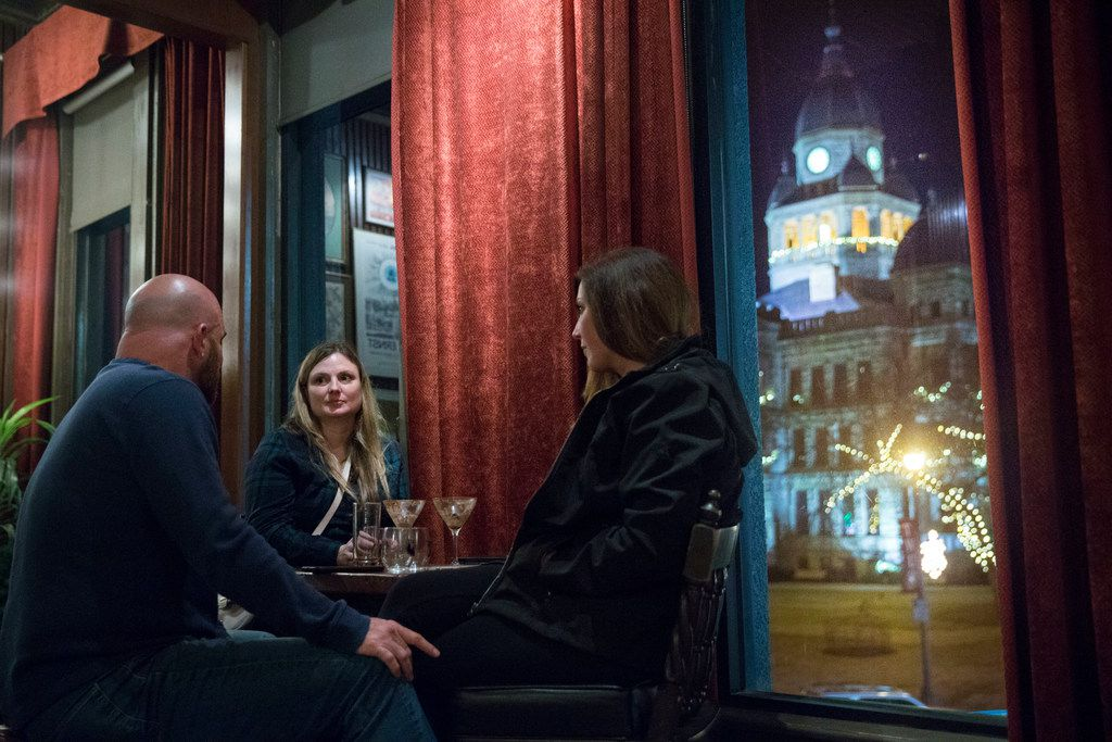 The Denton County Courthouse-on-the-Square Museum is visible as David Mitchell, left, and his wife Vered Mitchell, right, talk with Alexandra Bayer, center, at Paschall Bar located at Andy's Bar and Grill in Denton, Texas on Wednesday, November 28, 2018. Andy's will celebrate its 21 birthday on Saturday.