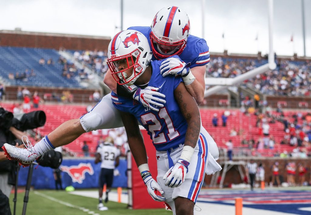 Southern Methodist wide receiver Reggie Roberson Jr. (21) and defensive end Gerrit Choate (52) celebrate a touchdown during a matchup between the Southern Methodist University Mustangs and the Navy Midshipmen on Sept. 22, 2018 at Gerald J. Ford Stadium in Dallas. (Ryan Michalesko/The Dallas Morning News)