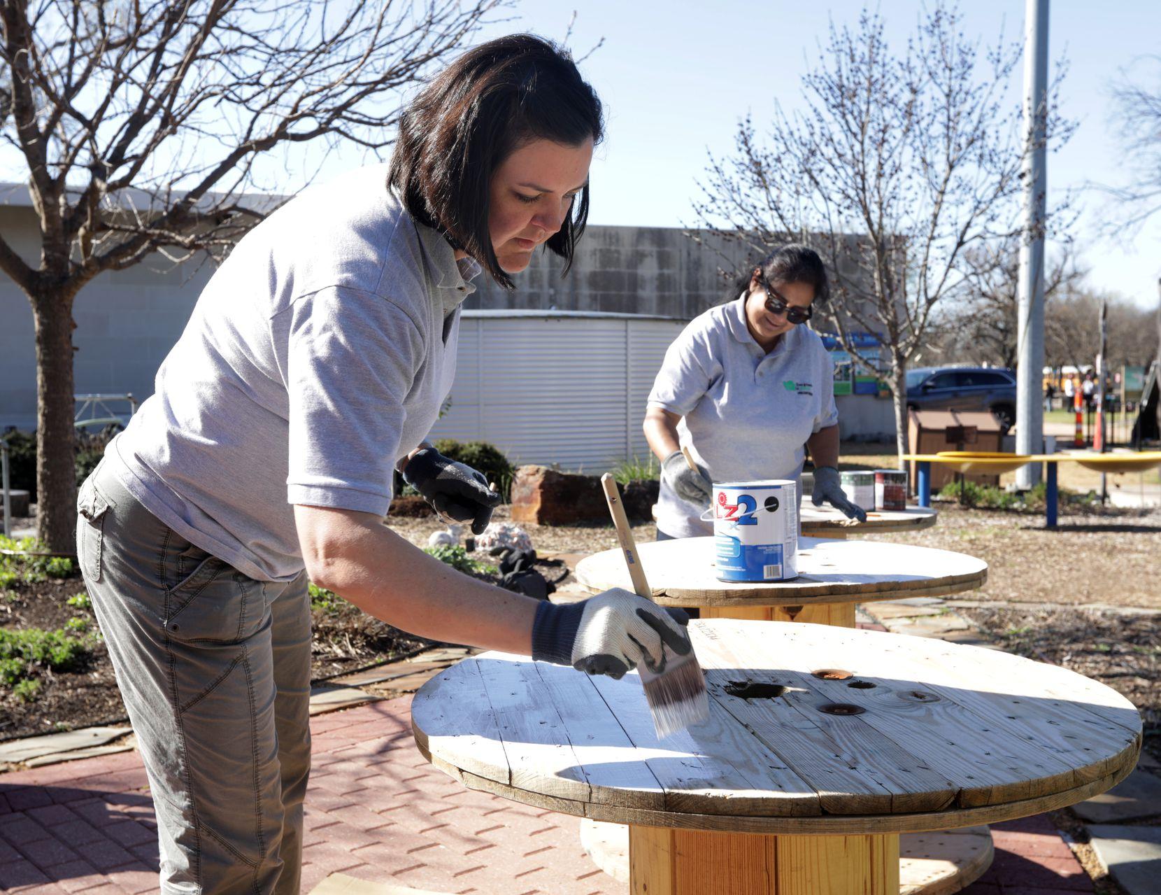 Jaime Bretzmann, left, and Nalini Joshi paint tables at the Environmental Education Center in Plano Thursday.