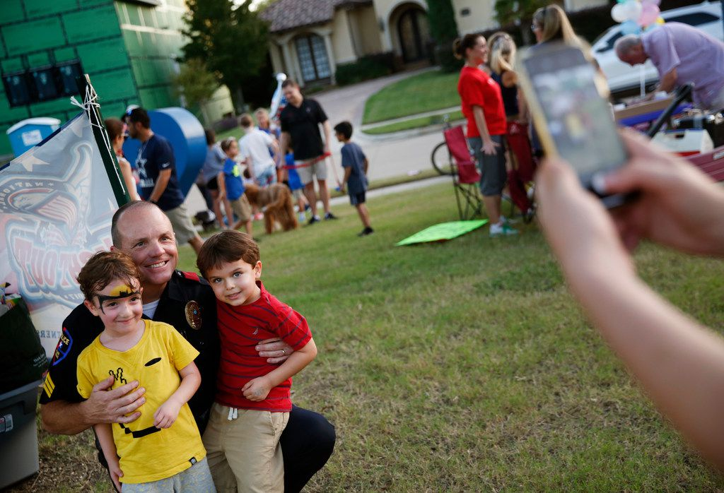 Plano police Sgt. Wes Gerig takes a photo with Aiden Kleyman, 4, (left) and Benjamin Black, 4, during National Night Out in the Kings Ridge neighborhood of Plano.
