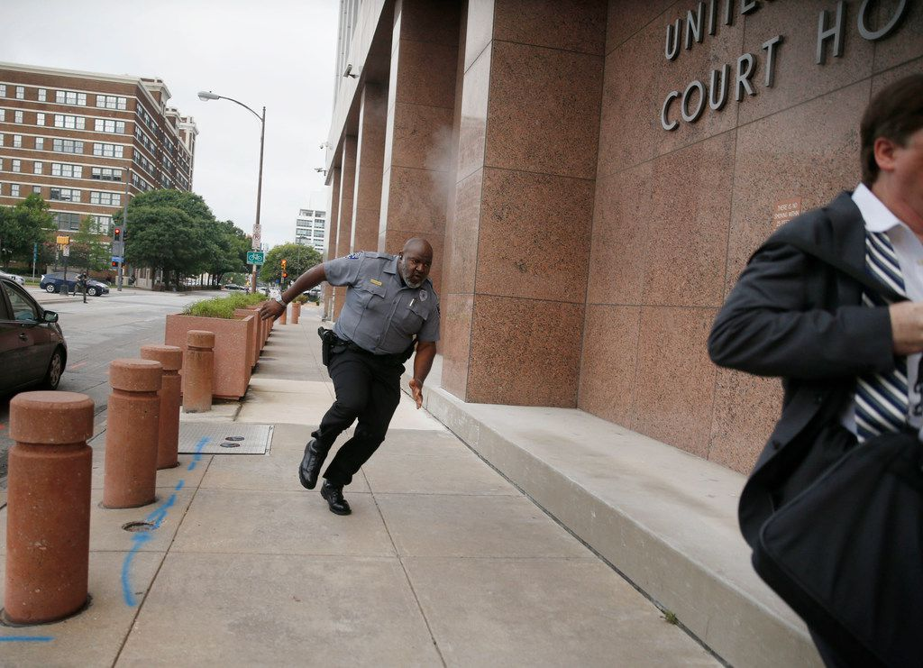 A security guard and a civilian run for cover as bullets ricochet off the building as a shooter (far background left) fires towards them on Monday morning, June 17, 2019 at the Earle Cabell federal courthouse in downtown Dallas. Law enforcement returned fire and the shooter was hit by gunfire. No officers or citizens were injured. FBI Special Agent in Charge Matthew Desarno identified the shooter as Brian Isaack Clyde, 22. Clyde died at the scene and was taken to Baylor University Medical Center, officials said. (Tom Fox/The Dallas Morning News)