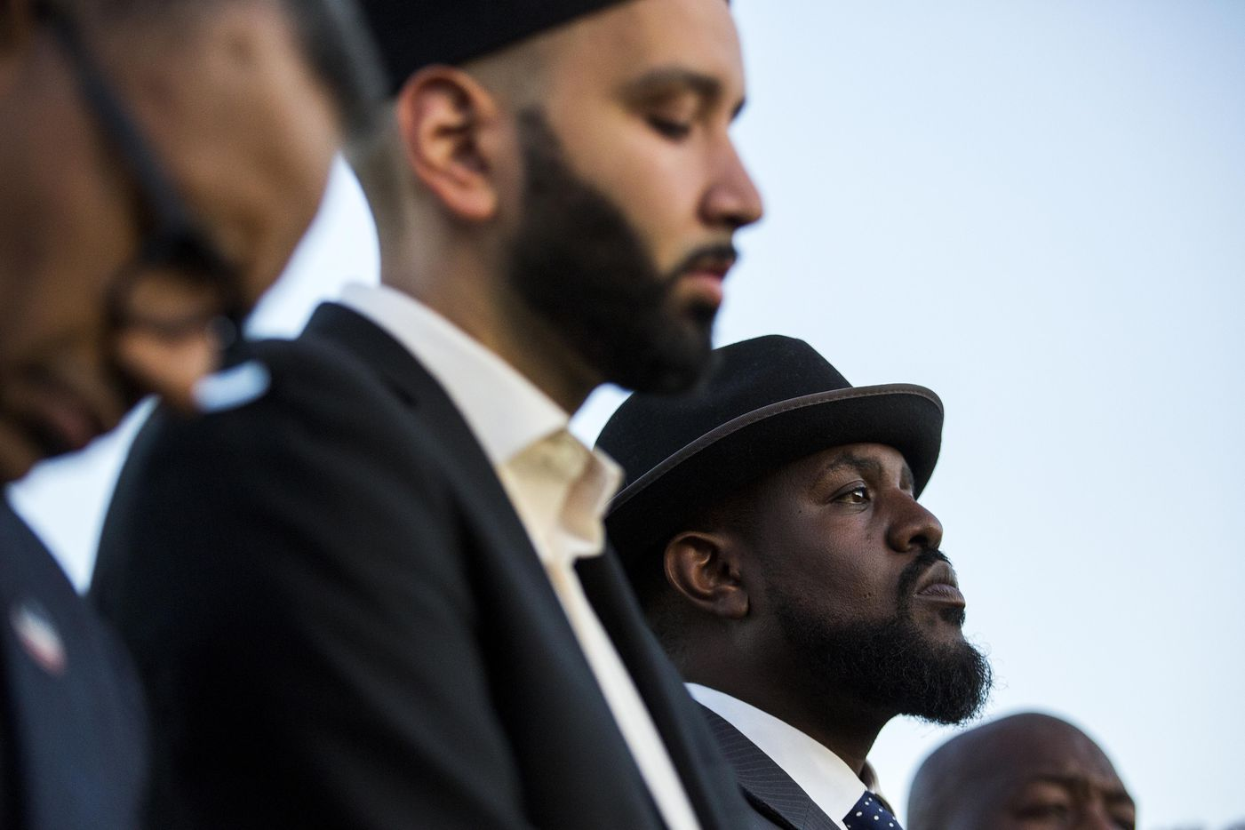 """Dr. Michael W. Waters (right) and Imam Omar Suleiman (center) listen to a speaker during the """"Remember His Name: Vigil for Jordan Edwards"""" candlelight vigil at Virgil T. Irwin Park on Thursday, May 4, 2017, in Balch Springs, Texas."""