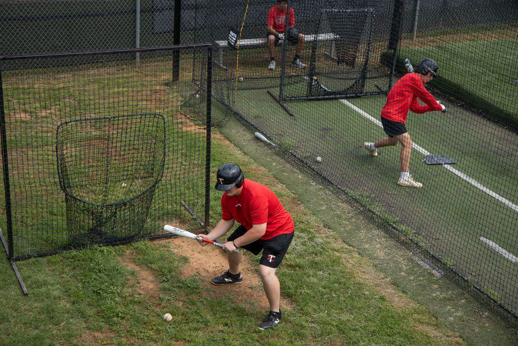 Players hit balls in batting cages during baseball practice at Euless Trinity High School in Euless, Texas Wednesday, May 22, 2019. (Shaban Athuman/Staff Photographer)