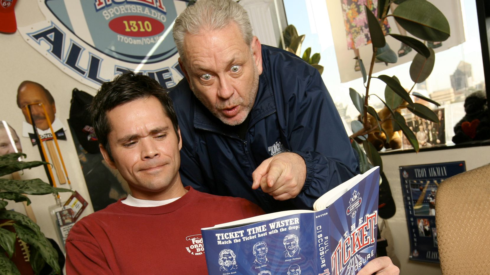 Corby Davidson (left) and Mike Rhyner look through a book at The Ticket offices in Dallas, TX, on Monday, January 5, 2009.