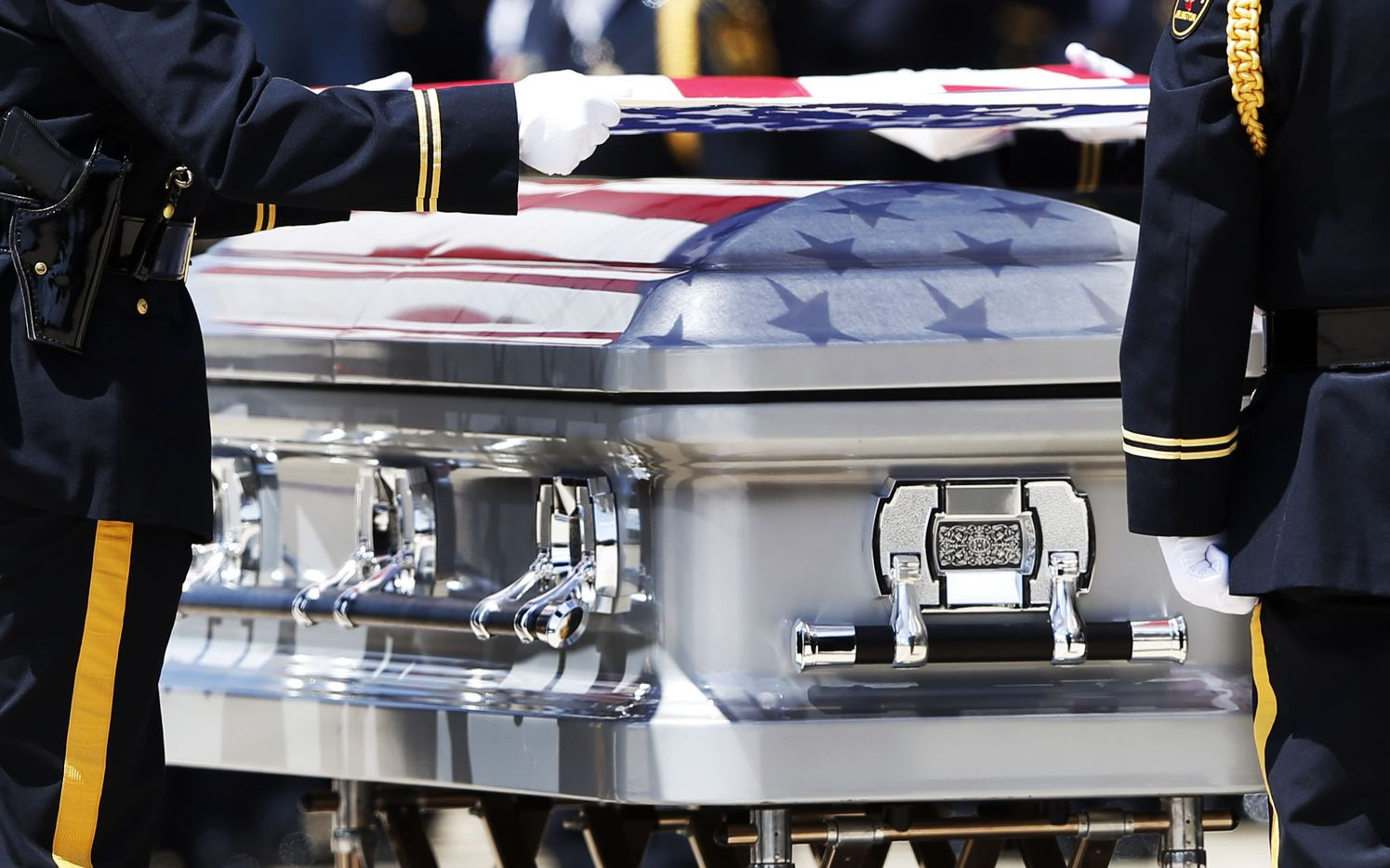 The colors of the Stars and Stripes are reflected on the coffin as the Arlington police Honor Guard prepares to fold the flag over the casket of DART Officer Brent Thompson during a memorial service at The Potter's House in Dallas on July 13, 2016. (Vernon Bryant/Staff Photographer)
