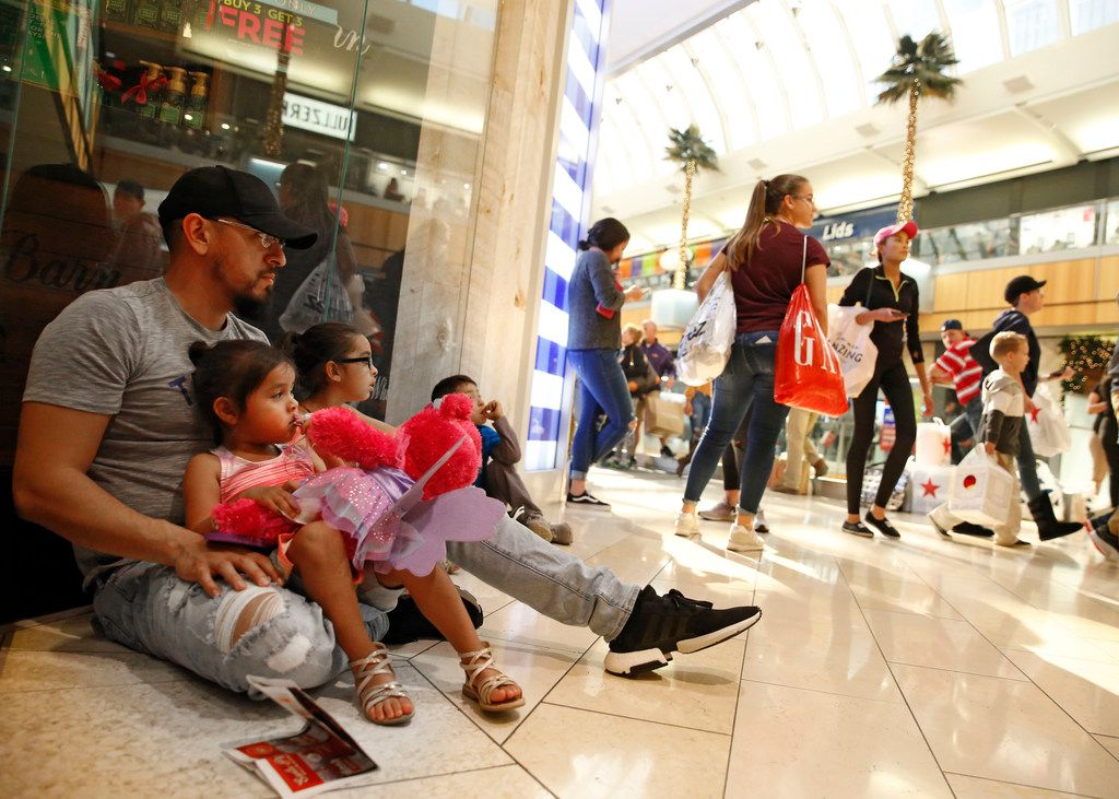 Ramiro Rodriguez (from left) with his family Mallory, 3, Alena, 6, and Elijah, 5, wait outside a store at Galleria Dallas in Dallas on Nov. 23, 2018. (Nathan Hunsinger/The Dallas Morning News)