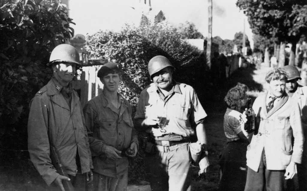 Ernest Hemingway and Col. David K.E. Bruce of the OSS, with a member of the French Resistance, August 1944. Hemingway wears a captured German belt and holds a glass, likely filled by the man on his left holding a bottle at the ready. From Writer, Sailor, Soldier, Spy, by Nicholas Reynolds.