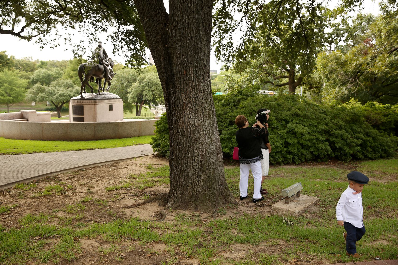 Matthew Chavez, 2, walks by as his mother Miranda Taddei (in floral headwear) gets ready for her marriage ceremony to Matthew Chavez near a statue of Confederate general Robert E. Lee at Robert E. Lee Park Aug.  16, 2017.
