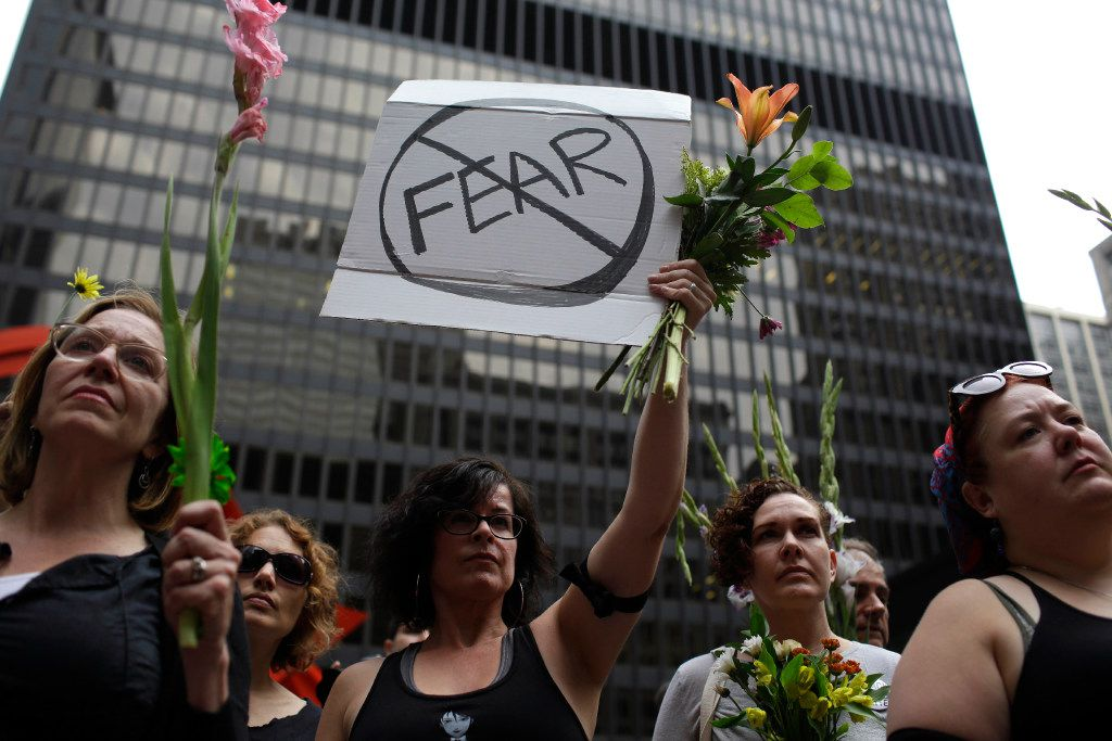 People hold flowers at a vigil August 13, 2017 in Chicago, Illinois for the victims in the previous day's violent clashes in Charlottesville, Virginia.  Heather Heyer, 32, was killed and 19 people injured in the city of Charlottesville when a car plowed into a crowd of people after a rally by Ku Klux Klan members and other white nationalists turned violent. Two state police officers died in a helicopter crash near the area.    / AFP PHOTO / Joshua LottJOSHUA LOTT/AFP/Getty Images
