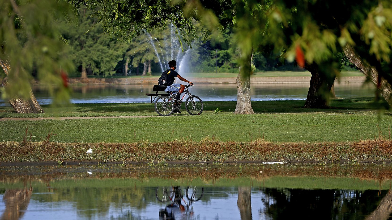 A man rides a bicycle at Towne Lake Recreation Area in McKinney, Texas, Tuesday, July 17, 2018. (Jae S. Lee/The Dallas Morning News)