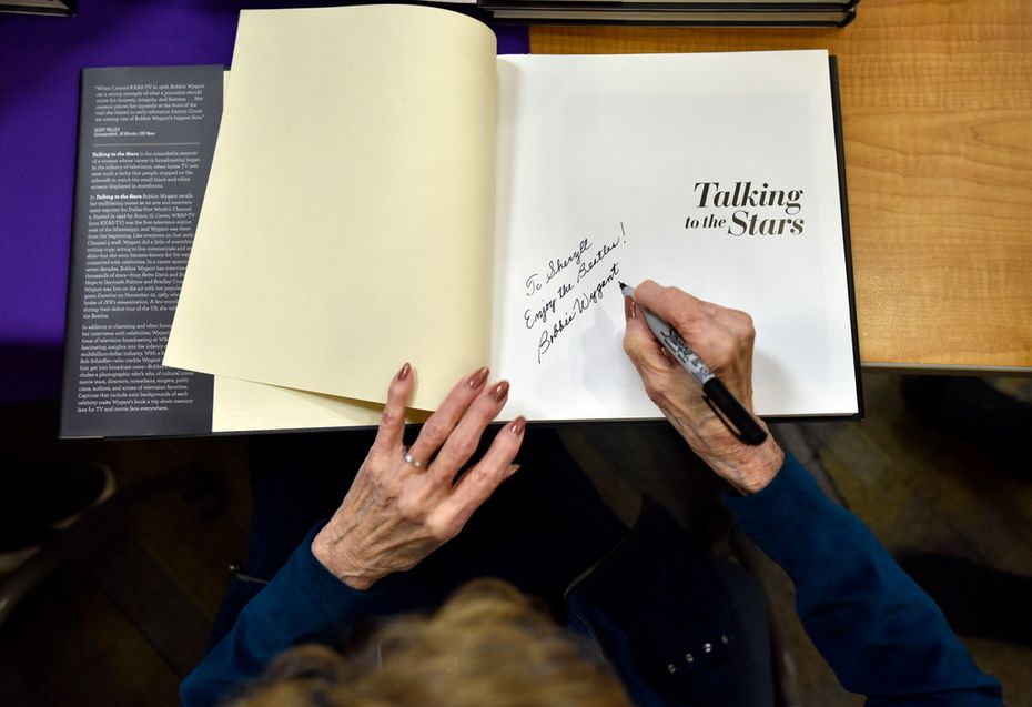 "Bobbie Wygant, 92, signs a copy of her book ""Talking to the Stars"" to a fan after speaking at the Oak Cliff Lions Club's  weekly luncheon on Dec. 19."