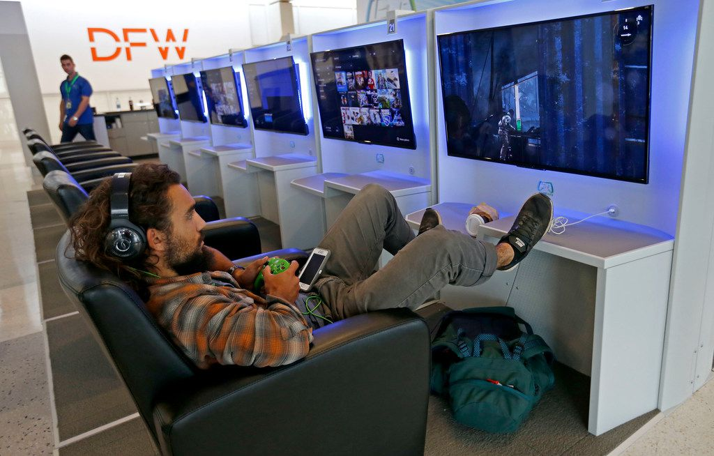 Traveler Conor Sandoval plays a video game at Gameway inside Terminal E of Dallas/Fort Worth International Airport in DFW Airport, Texas, Friday, July 6, 2018. He has a 22 hour layover heading to Chile from Seattle.