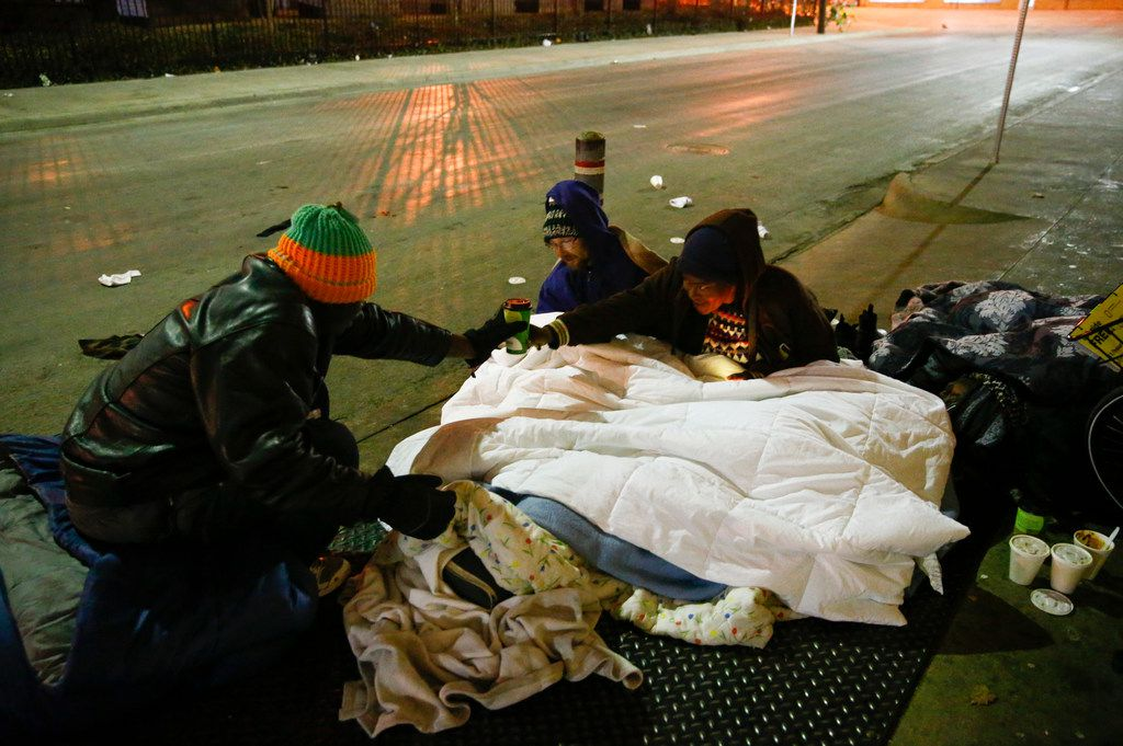 Dawaylon Raymond (from left) provided some donated coffee as Ryan Rule and his wife, Deshonda Rule, slept on top of an exhaust vent next to The Stewpot on Park Avenue in downtown Dallas on Jan. 16, 2018.