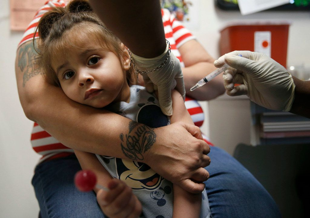 Karma Islas, 2, is held by her mother Maria Islas of Dallas as she gets a shot for a vaccine at the Dallas County Health & Human Services immunization clinic in Dallas on Friday, March 8, 2019.