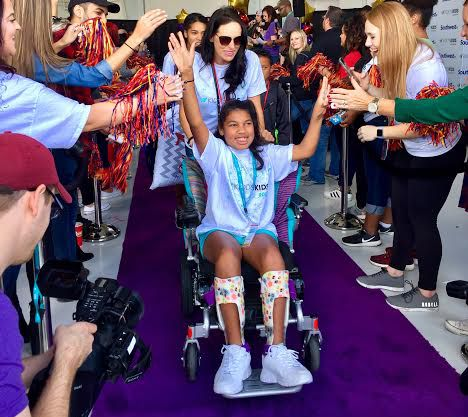 Overjoyed kids from 2016's Kidd's Kids trip to Orlando race down the purple carpet toward the plane that will jet them off to Walt Disney World. Now, teenagers will be invited on the trip.