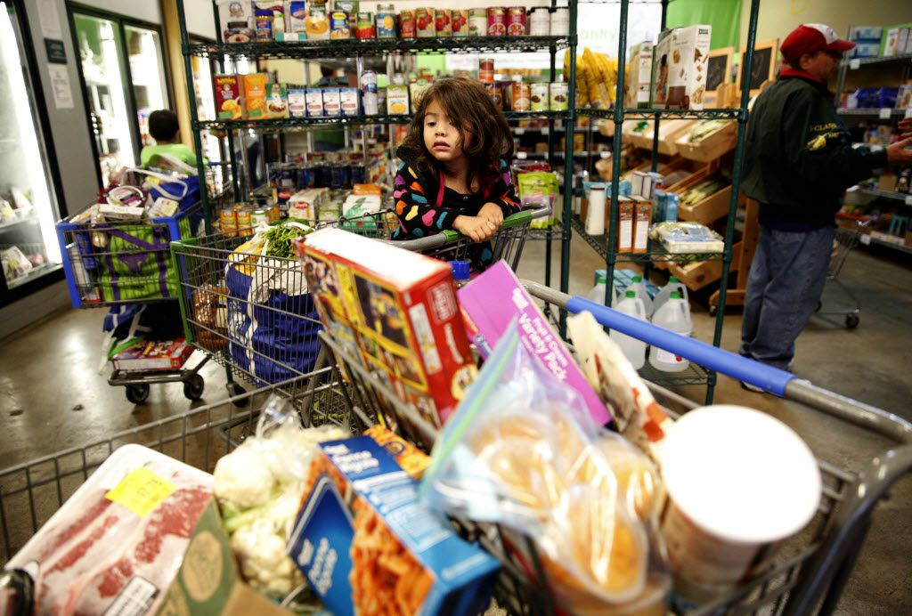 Daenelly Rodriguez waited for her mother as she shopped in the food pantry at the Allen Community Outreach in November 2015.