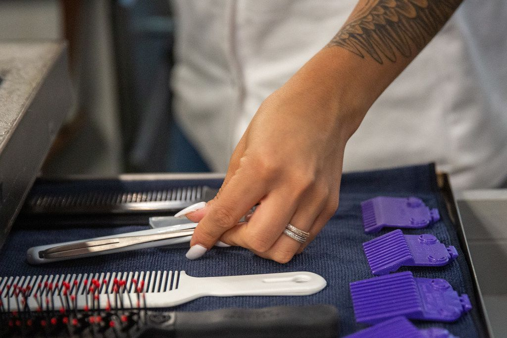 Student Megan Yruegas prepares her barbering station at the Blade Craft Barber Academy in the Deep Ellum neighborhood of Dallas on Thursday, Aug. 1, 2019.