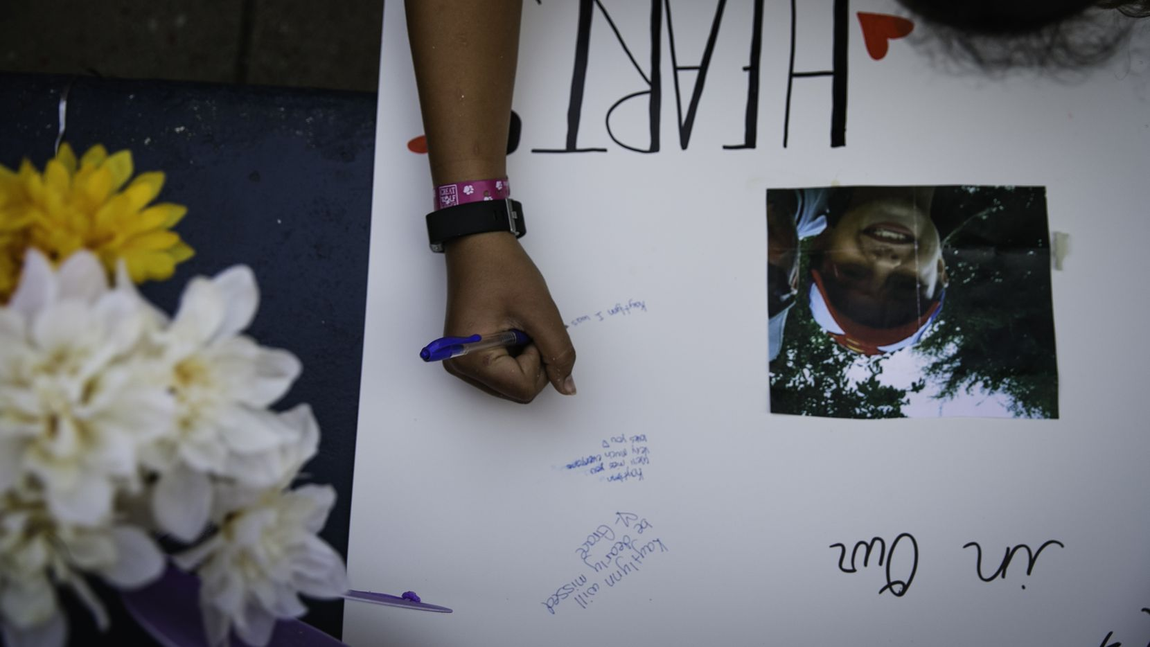 A vigil attendee signs a poster in honor of Kaytlynn Cargill at Central Junior High School in Euless.