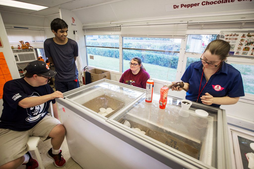 From left: Employees Coleman Jones, Trey Davis-Hale and Courtney Cebern talk while Lindsey Riddell pours chocolate syrup on ice cream at Howdy Homemade Ice Cream at the State Fair of Texas.