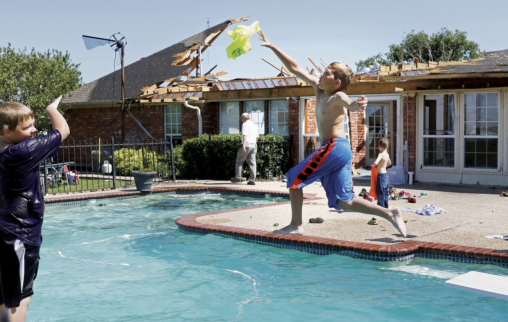 Jacob Campbell (left), 10, threw a wet T-shirt to Dax Foster, 10, as they swim at a home in the 200 block of Stark Lane in Sherman on April 27. The boys swam a day after a tornado took off part of the home's roof.