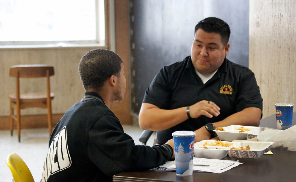 Dallas Police Officer Victor Guardiola (right) talks with Carter High School student Sedric Owens on Dec. 13, 2018, as part of a mentoring program at the school. Guardolia was also mentored by a police officer when he was a teen.