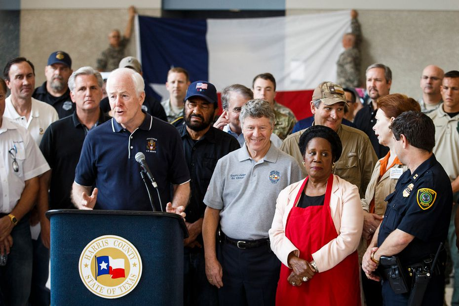In this file photo, Sen. John Cornyn is surrounded by fellow lawmakers and law enforcement as he addresses a press conference at the evacuation center at NRG Center on Monday, Sept. 4, 2017, in Houston. A group of elected officials met with evacuees and held a brief news conference in an effort to drum up support for emergency aid for Harvey victims. (Smiley N. Pool/The Dallas Morning News)