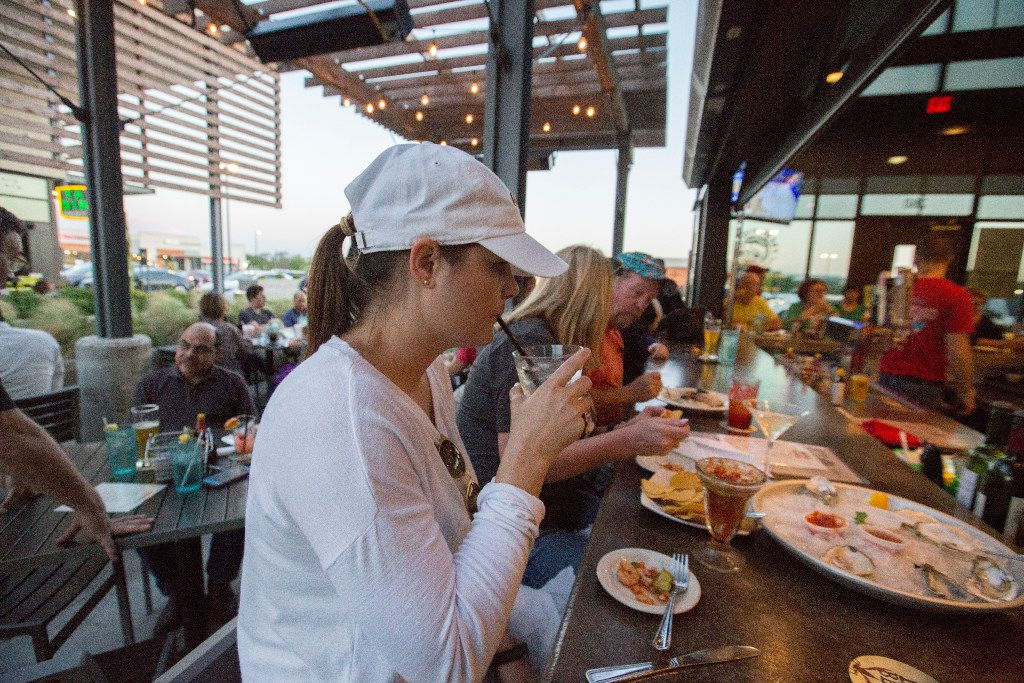 Dana Eldridge, center, takes a sip of her drink at the peninsula bar Fish City Grill in Richardson .(Ron Baselice/The Dallas Morning News)