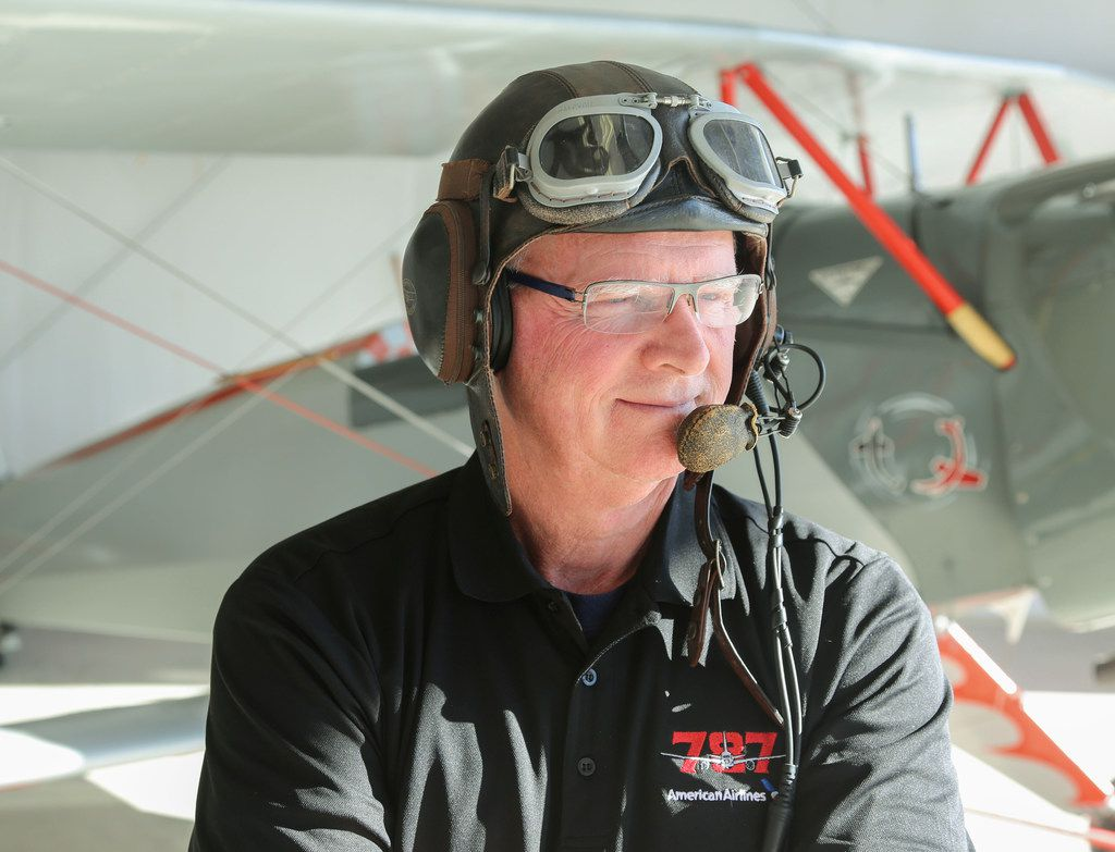 Retired American Airlines pilot Caption Jeff Rowland poses with1934 Bucker Jungmann at Hicks Airfield in Fort Worth Wednesday, January 31, 2018 that he updated in 1978 with an American instruments and engine. He is wearing the helmet he uses when flying the plane. (Ron Baselice/The Dallas Morning News)