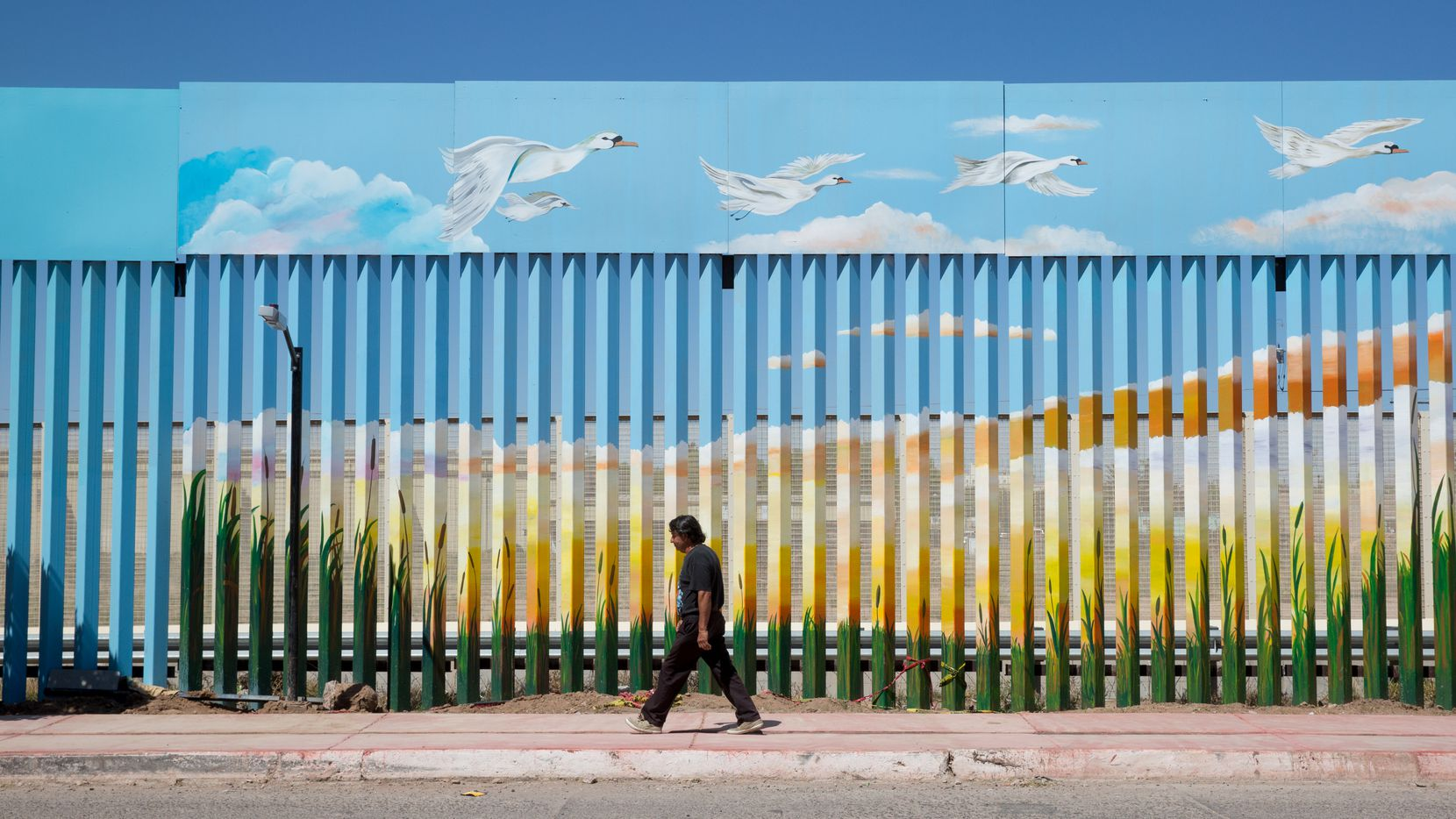 A man walks past the painted border fence in Agua Prieta, Mexico across the border from Douglas, Ariz. A man walks past the painted border fence in Agua Prieta, Mexico.