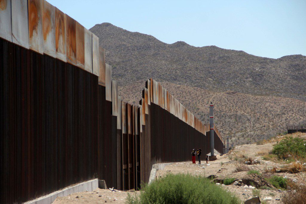 A Mexican family stands next to the border wall between Mexico and the United States, in Ciudad Juarez, Mexico.