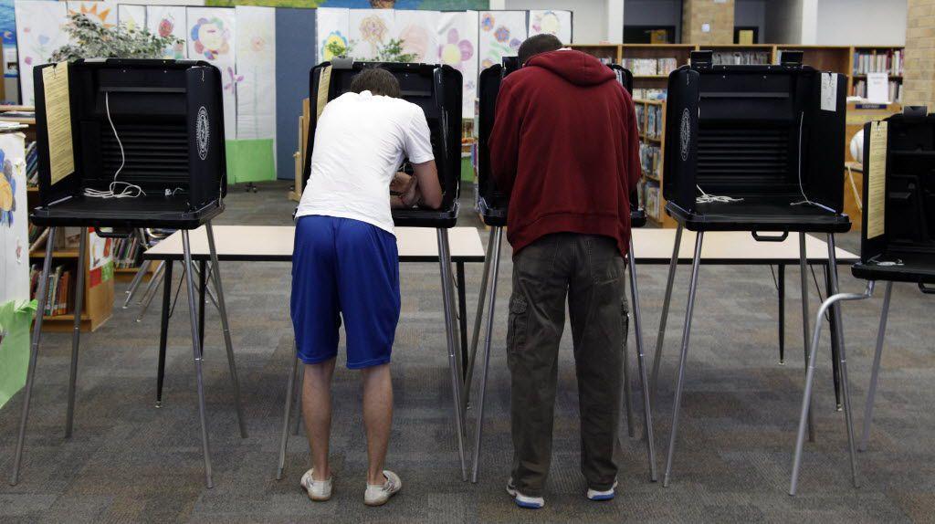 Austin Rivard, 18, left, votes next to his father, Dana Rivard at Sherrod Elementary School in Arlington on November 6, 2012.