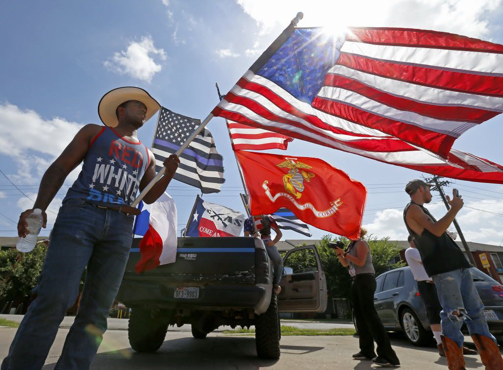 Counter protester Joseph Offutt (left) holds an American flag in a group of counter protest standing across a Black Lives Matter demonstration on Park Lane in Dallas, Sunday, July 10, 2016. (Jae S. Lee/The Dallas Morning News)