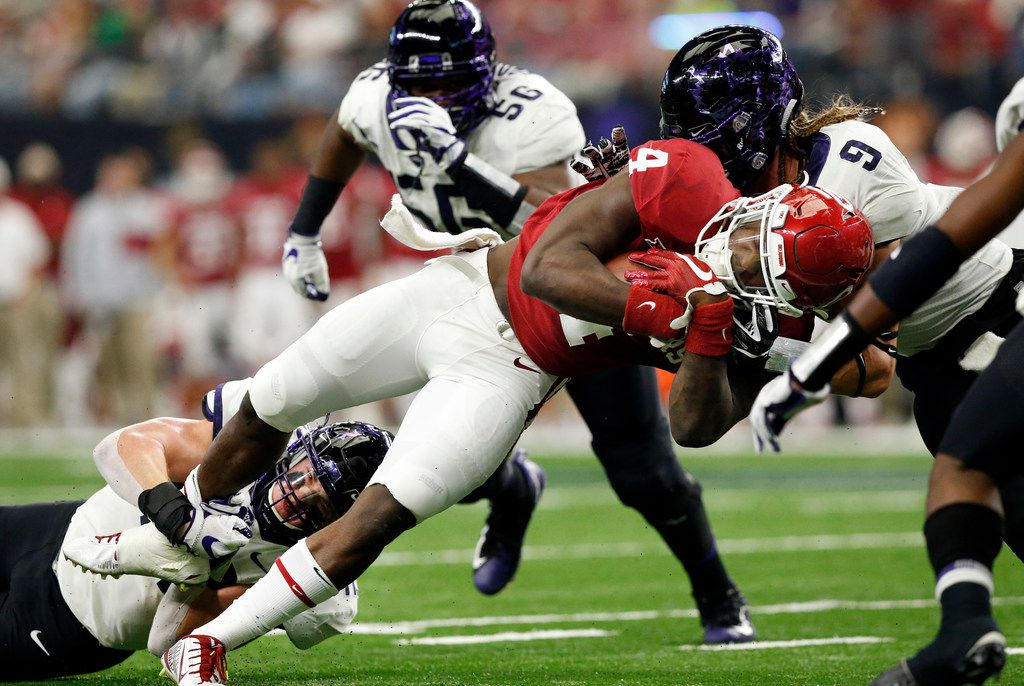 It takes TCU Horned Frogs linebacker Ty Summers (42) and defensive end Mat Boesen (9) to bring down Oklahoma Sooners running back Trey Sermon (4) during the first quarter of the Big XII Championship game at AT&T Stadium in Arlington, Texas, Saturday, December 2, 2017. (Tom Fox/The Dallas Morning News)
