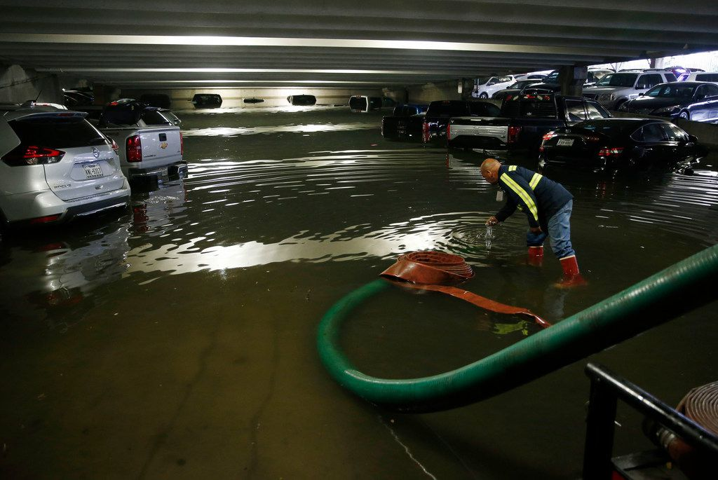 City of Dallas employee Holvin Rivera Reyes removes debris as water is pumped out of the lower level of parking garage A at Dallas Love Field in Dallas on Wednesday, April 23, 2019. The airport closed the lower level to traffic. Water is being pumped from the flooded areas by city staff employees. (Vernon Bryant/The Dallas Morning News)