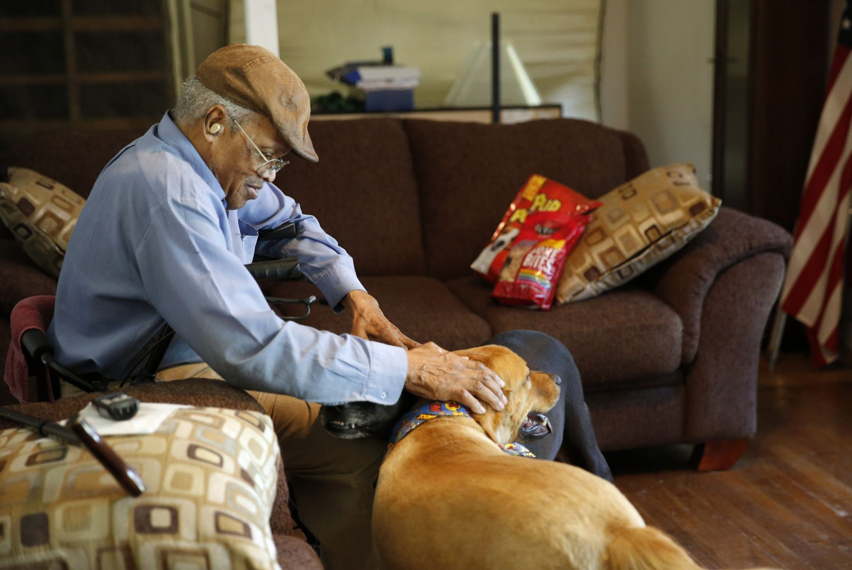 James Evans, 83 pets his dogs Rex (left) and Renny (right) at his home in Dallas, on Saturday, July 13, 2019.