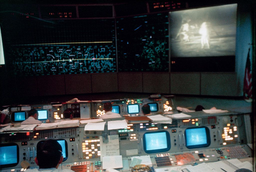In this July 20, 1969 photo made available by NASA, flight controllers work in the Mission Operations Control Room in the Mission Control Center during the Apollo 11 lunar extravehicular activity. The television monitor shows astronauts Neil Armstrong and Buzz Aldrin on the surface of the moon.