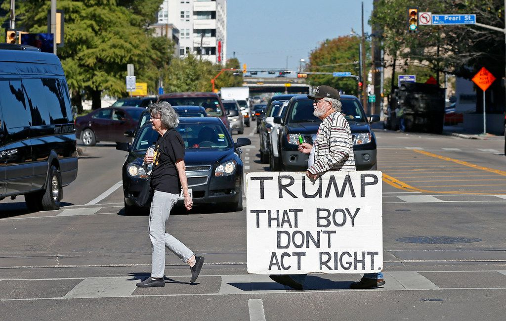 Protester Gale McCray (right) crosses Ross Avenue on the way to join other protesters near the Belo Mansion where President Donald Trump participates in a roundtable with RNC supporters on Wednesday, Oct. 25, 2017, in Dallas. (Jae S. Lee/The Dallas Morning News)
