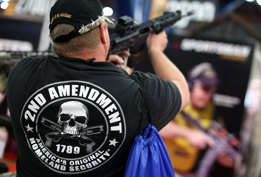 An attendee inspectss an assault rifle during the 2013 NRA Annual Meeting and Exhibits at the George R. Brown Convention Center in Houston