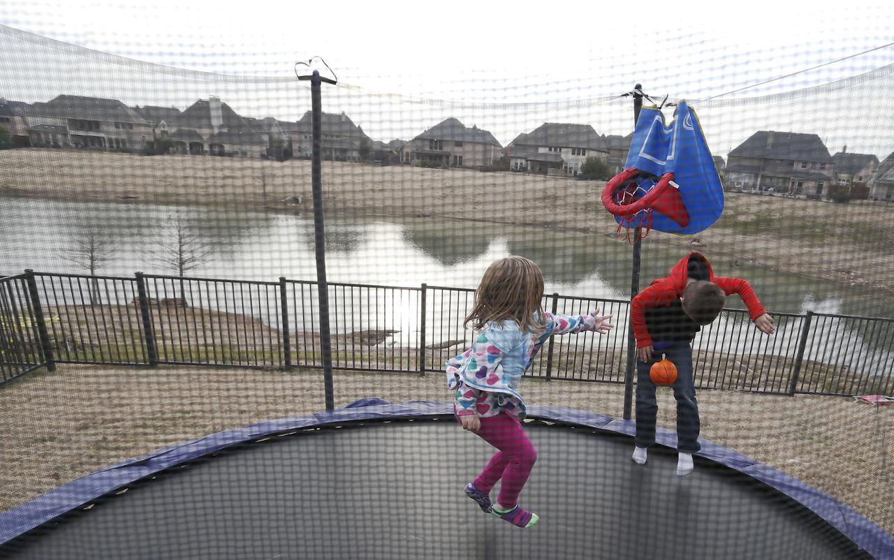 Gavin Woodward, 8 and Riley Woodward, 5, play on the trampoline in the backyard in Frisco on Wednesday, January 20, 2016. The backyard faces a six-acre open space that slopes down from their fence to a pond. The problem continues to escalate while the HOA and developer argue over who's responsible.