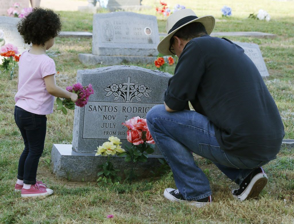 Roberto Corona, right,  and his daughter, Sophia, 2, places flowers at Oakland Cemetery on Friday, July 24, 2015 in Dallas to remember Santos Rodriguez who was killed 42 years ago by a Dallas police officer.