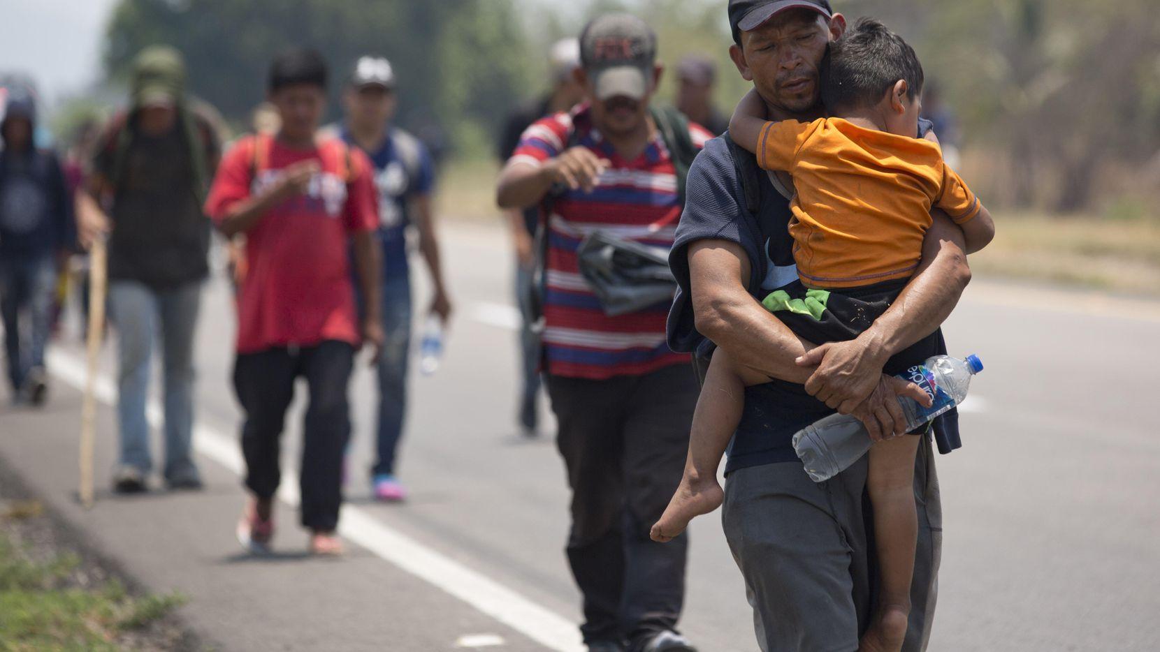 Un migrante de Centroamérica carga a un niño en brazos en una carretera cerca de Tonalá, Chiapas el 21 de abril. (AP/Moises Castillo)