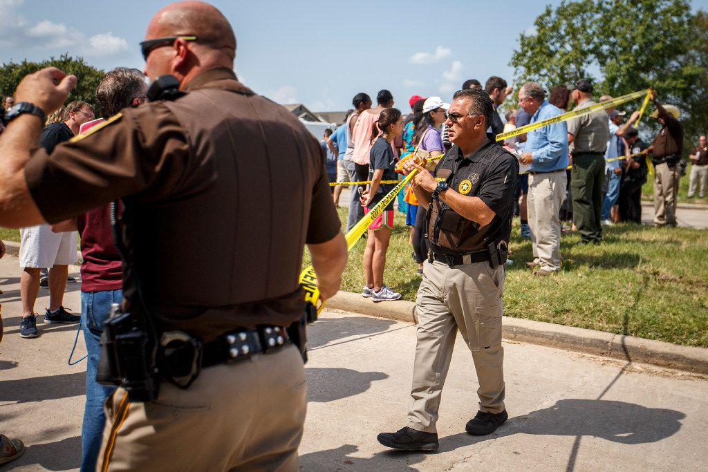 Law enforcement officer put up police tape in front of a group residents of the Cinco Ranch Canyon Gate subdivision on Saturday, Sept. 2, 2017, in Katy.
