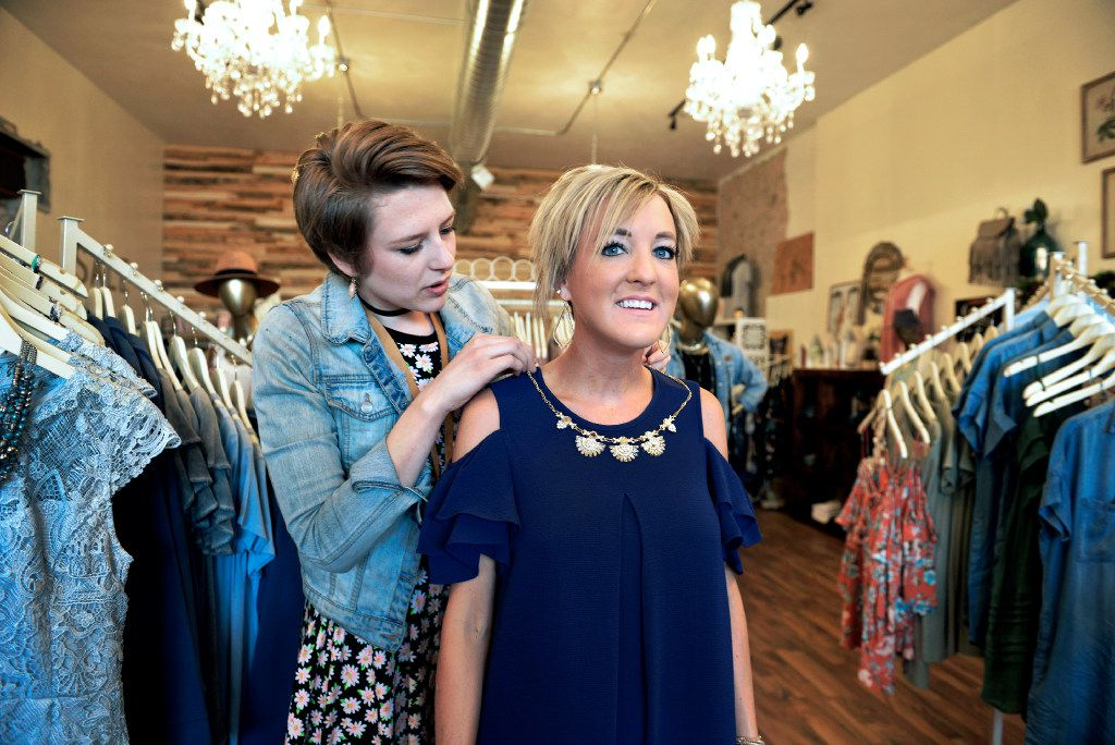 Sarah Henning, left, assistant manager at a clothing boutique, helps fit Kayla Delzer with outfits for her speaking engagements in Fargo, N.D., April 10, 2017. Many tech companies are competing to get their apps and products into classrooms. (Dan Koeck/The New York Times)