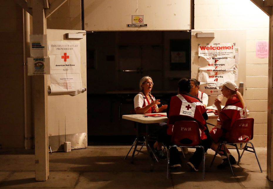 Red Cross volunteers sit at the entrance of an evacuation shelter Friday in Pahoa, Hawaii.