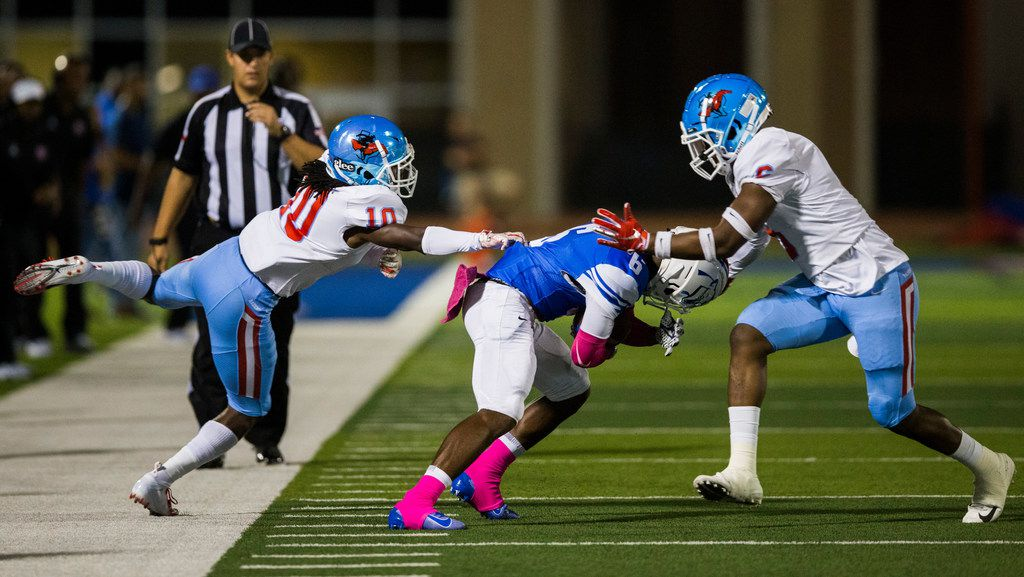 Duncanville wide receiver Marquelan Crowell (6) is tackled by Skyline defensive back Milton Roundtree (10) and linebacker Damajai Stephens (6) during the first quarter of a high school football game between Skyline and Duncanville on Friday, October 4, 2019 at Panther Stadium in Duncanville. (Ashley Landis/The Dallas Morning News)