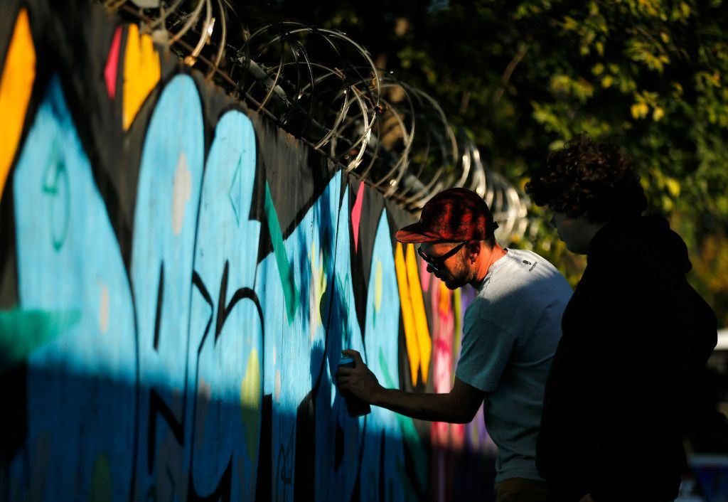 An artist creates spray art on a wooden fence Saturday at The Fabrication Yard in West Dallas during Go Paint Day, two days dedicated to celebrating hip hop history month with paint, music, dancing and community.